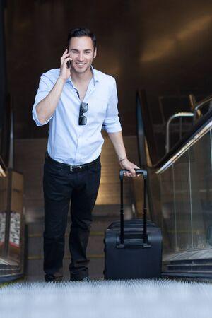 travel bag: Man with trolley walking outside metro