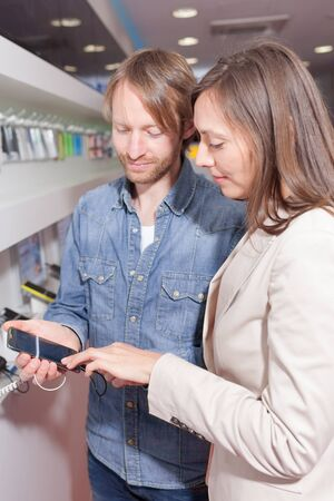 assistent: Choosing a phone in a cell phone shop Stock Photo