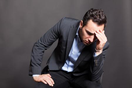 sitting man: Dark-haired man thinking