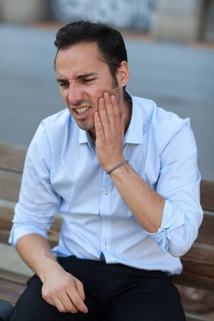 man having toothache outside