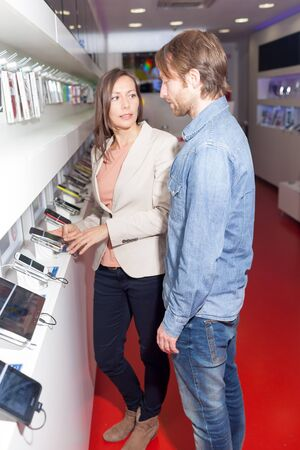 assistent: Shop assistant helping a customer choosing a smart phone