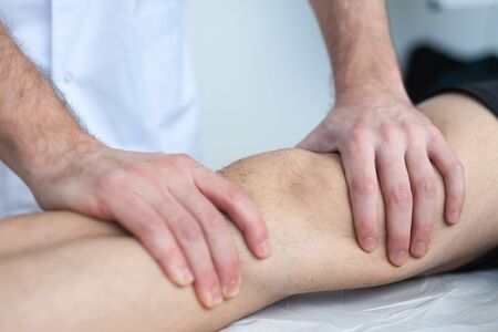 muscle strain: knee massage Stock Photo