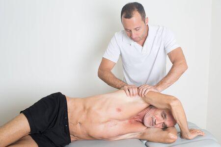 homme massage: physiothérapie avec un sujet âgé