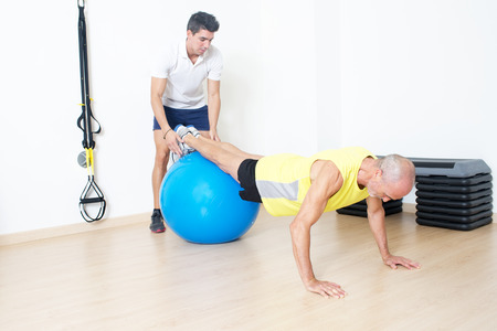 fitness ball: Coach helps senior with fitness ball exercise