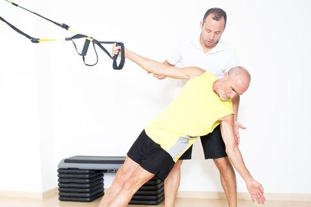 fisioterapia: El entrenador ayuda al hombre mayor con el ejercicio trx Foto de archivo