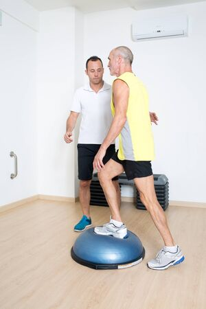 strenghten: Coach helps senior with bosu exercise