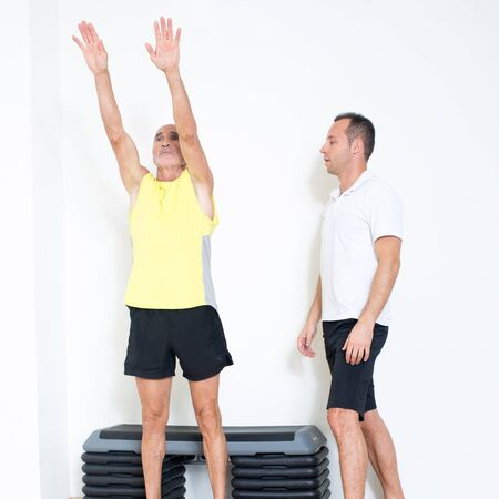 functional: Pensioner making a stretching exercise with coach