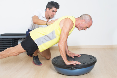 helps: Coach helps senior with fitness exercise