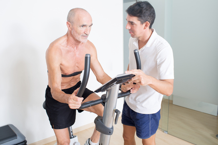 man legs: Coach helps senior with spinning exercise