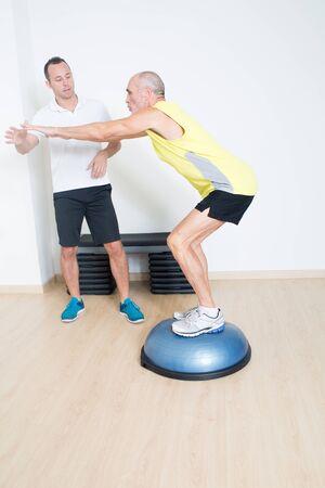 Coach helps senior with bosu exercise