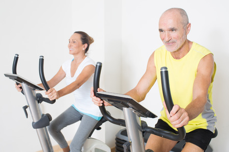 functional: Elderly couple having fun while cycling in gym Stock Photo
