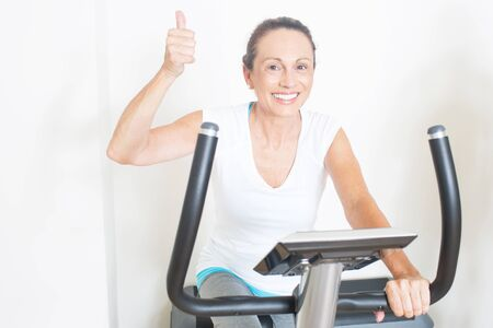 likes: Elderly woman likes cycling in gym Stock Photo