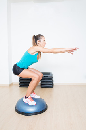 squatting down: Woman making squats on balance trainer