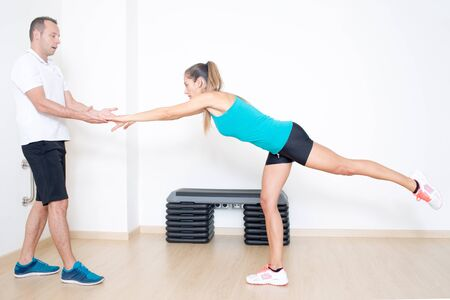 strenghten: Coach helping with fitness exercise Stock Photo