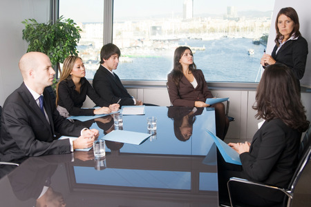 Certaines personnes regardent une femme d'affaires écrit sur un tableau lors d'un atelier d'affaires dans un bureau de panorama Banque d'images