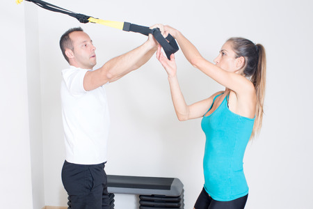 strenghten: Personal trainer helps with suspension training exercise
