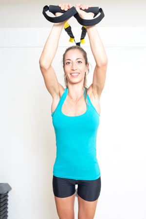strenghten: Athletic woman makes TRX exercise