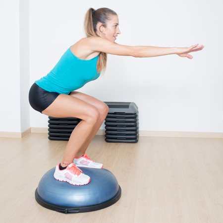 Woman making squats on balance trainer