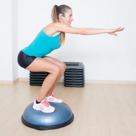 Femme faisant des squats sur l'équilibre formateur