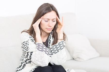 dolor de cabeza: Mujer con dolor de cabeza en el sof�