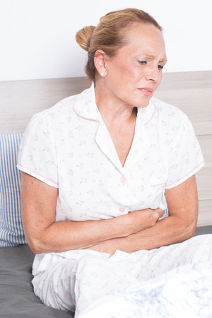 senior pain: Elderly woman with stomachache Stock Photo