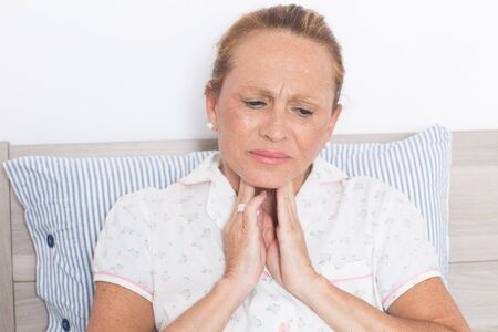 cold sore: Elderly woman in bed with sore throat