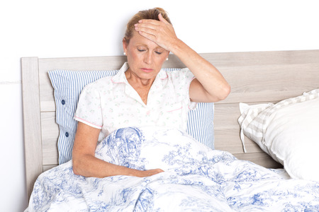 Elderly woman with headache in bed