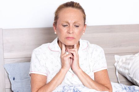 Elderly woman in bed with sore throat