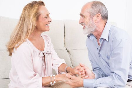 into: Happy elderly couple holding hands and looking into their eyes