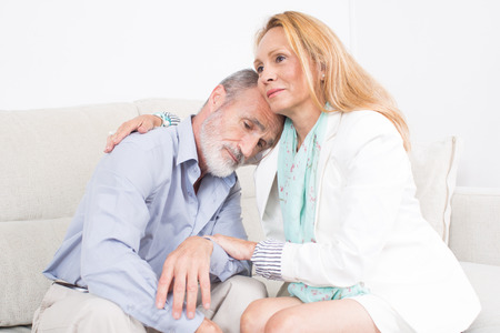 solace: Elderly woman comforting an older man sitting on the sofa