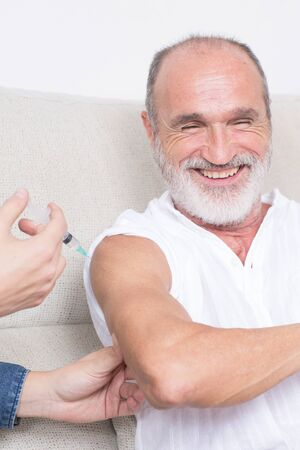 vaccines: Elderly man having fun during vaccination Stock Photo