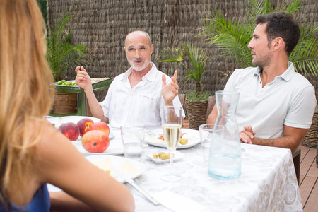 sun: Father explaining a story during lunch Stock Photo