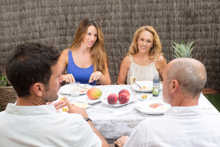 Family with four persons eating outside