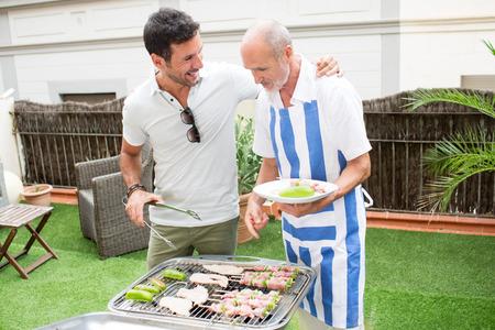 Elderly son preparing barbecue with his father Standard-Bild