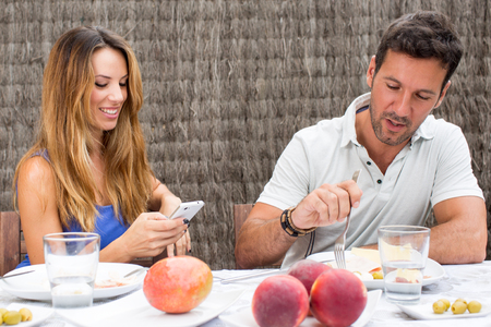 solace: Woman texting while man eating Stock Photo