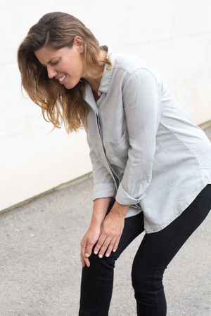 de rodillas: Mujer atractiva que tiene dolor en la rodilla al caminar