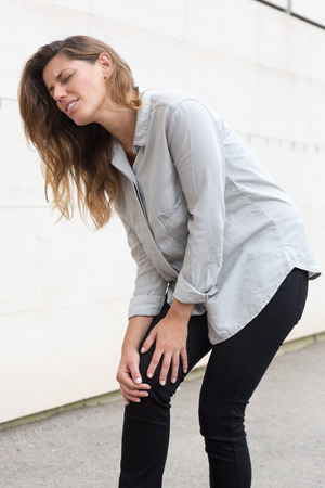 girl shoes: Attractive woman having knee pain while walking