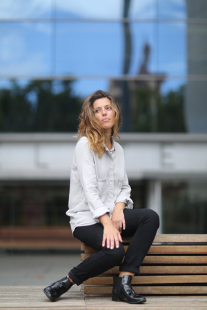 sitting on a bench: model sitting on bench having fun Stock Photo