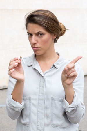quiting smoking: Woman breaking a cigarette symbol picture for quiting smoking