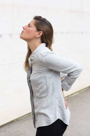 woman in pain: Attractive woman with back pain outside Stock Photo