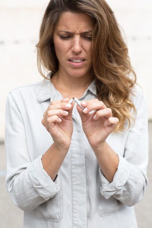 quiting smoking: woman breaks a cigarette as a symbol picture for quiting smoking Stock Photo