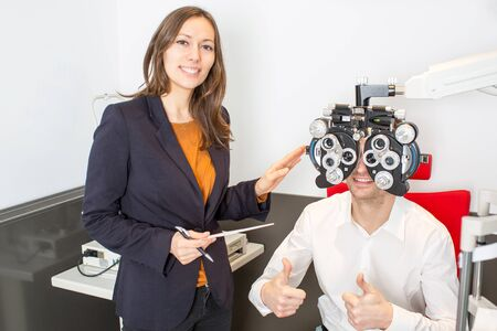 eye care professional: man during an eye exam with thumb up Stock Photo