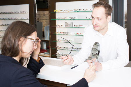 assistent: Customer service when buying glasses in an optician shop Stock Photo