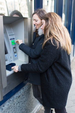 withdrawing: Two women withdrawing money