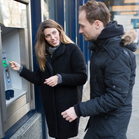 withdraw: Woman and man at ATM Stock Photo