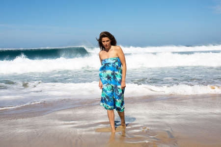 strongly: Pretty woman in turquoise dress on the beach Stock Photo