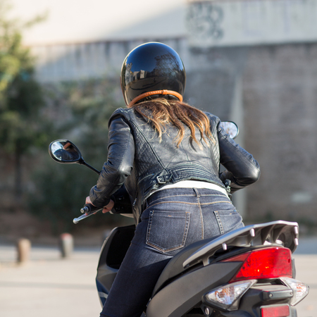 woman starts moped from the back