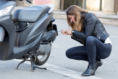 inoperative: woman repairs a scooter