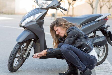 repairs: woman repairs a scooter