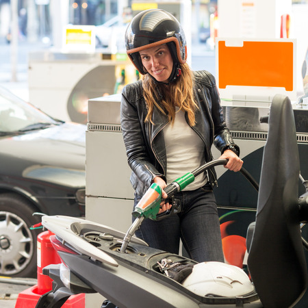 refuel: Woman fueling scooter at the gas station Stock Photo